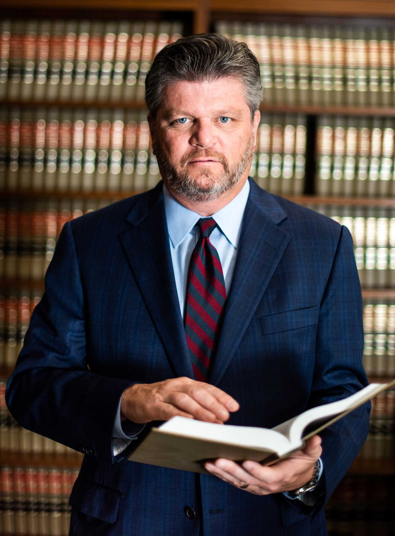 John Harralson holding a book standing in front of shelves of law books