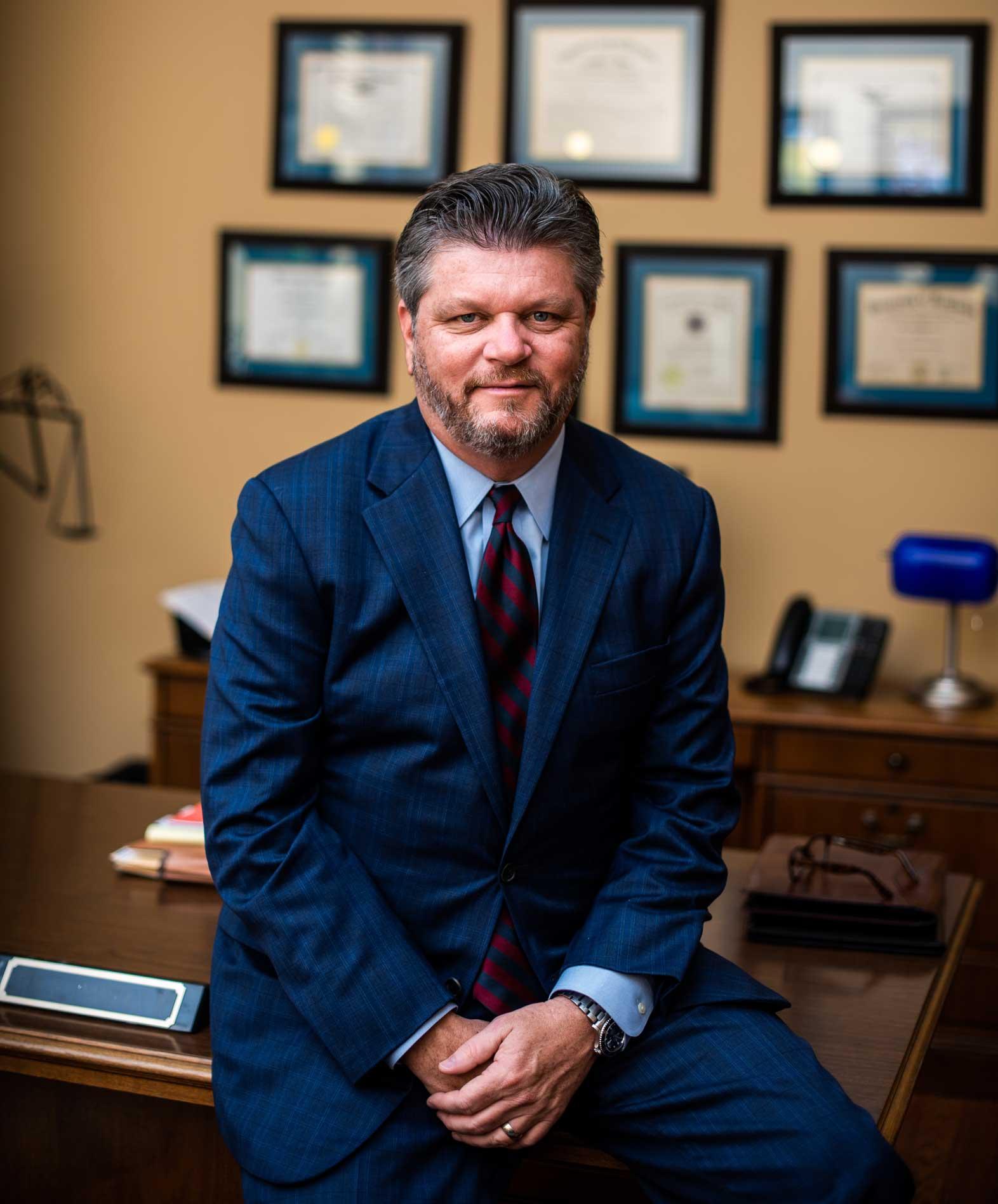 John Harralson leaning against his desk smiling